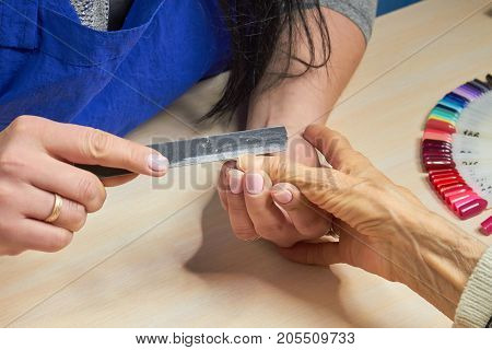 Beautician filing nails to client. Woman hands in nail salon receiving manicure. Old woman is getting manicure in a beauty salon.