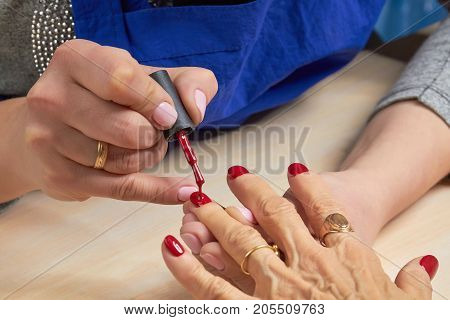 Woman applying red varnish to finger nails. The process of painting female nails with red varnish by manicurist in beauty salon.