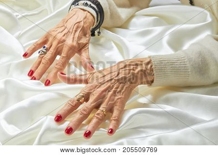 Senior manicured hands with jewelry on silk. Old aristocratic woman hands with beautiful red manicure wearing luxury rings, white silk. Female treatment and wealth.