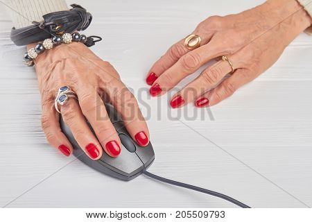 Female hands working with computer mouse. Businesswoman hands with luxury jewelry using computer mouse, white background.