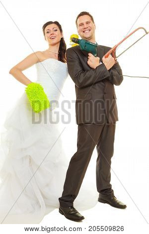 Taking care of house together sharing household duties concept. Bride in wedding dress and groom wearing elegant suit holding cleaning equipment and tools.