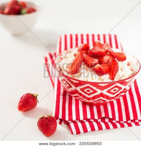 Healthy breakfast: Cottage cheese and strawberries in white bowl
