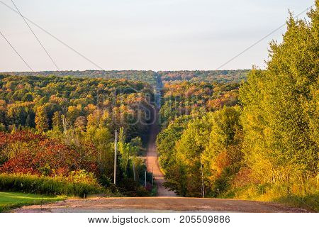 Steep gravel road going through a colorful Wisconsin forest in early autumn