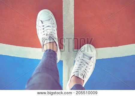 Women's legs in white sneakers are standing on the choice of whether to go left or right.