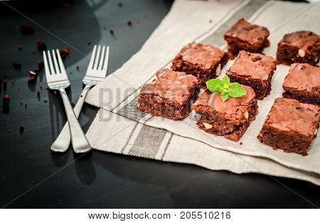 homemade, chocolate brownie with hazelnuts and almonds on a black background