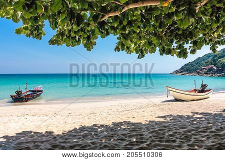 Two boats at the white sand beach of the tropical blue sea. Daytime, Haad Yuan, Koh Phangan, Thailand