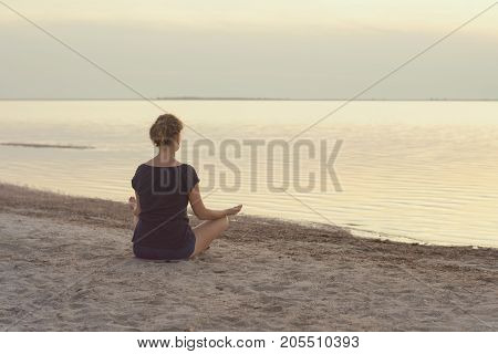 A girl sits on the lake shore and meditates