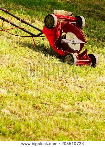 Broken Old Lawnmower In Backyard Grass