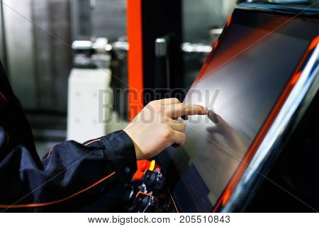 The operator adjusts modern CNC lathe machine using the touch screen. Selective focus.