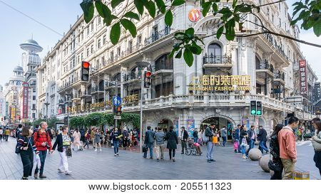 Shanghai, China - Nov 4, 2016: Along Nanjing Road Pedestrian Street - Buildings with colorful lights in western architectural designs. At the Shanghai Fashion Store. People walking about.