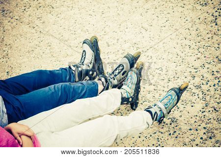 Closeup of people friends with roller skates. Woman and man relaxing outdoor.