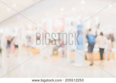 Abstract blur shopping mall and department store interior with people walking for background.