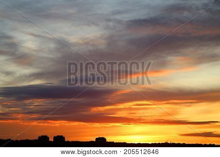 Photo of a brightly beautiful sunset with clouds over the city of autumn
