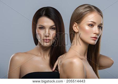 two beautiful young women with natural glowing makeup and long straight hair. beauty shot on gray background. copy space.