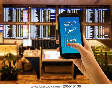 Traveler smartphone app concept. Close up of woman hand in international airport use mobile phone for check in online with flight information board background checking her flight. Anonymous face