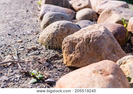 border of stones near the walkway. nature peace.