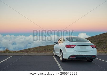 White car in beautiful mountains with scenic view above the clouds at sunset or sunrise