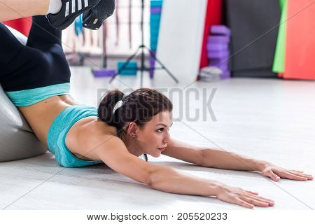 Young brunette stretching her back trying to reach head with feet from laying position with arms extended forward in sports club.