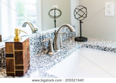 Closeup Of Modern Bathroom Sink With Granite Countertop, Mirror, Soap Dispenser Pump And Faucet In S