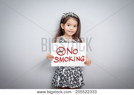 little cute girl with handwriting text no smoking on white paper. no smoking sign. stop smoking symbol. stop smoking. quitting from addiction concept.