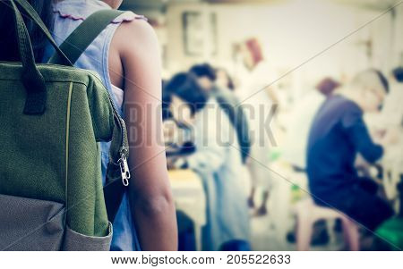 Girl with backpack entering to the art classroom Education concept.