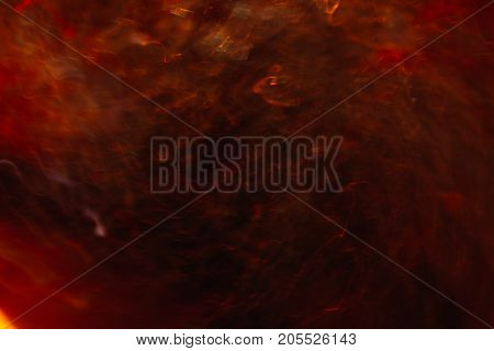 Abstract background of colorful crankles in motion on black. Bokeh of defocused curves, blurred neon yellow and red leds, hellfire and storm, abyss and seven circles of hell