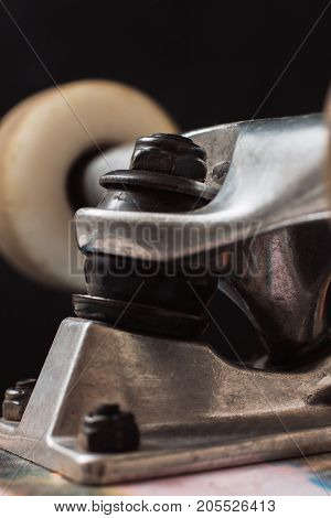 Close up of skateboard parts on black background. Safety construction of professional extreme sport devices and skateboarding elements. Kingpin, bushing, hanger, wheel