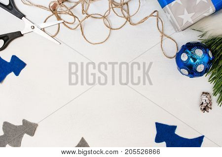 Festive background of Christmas present decoration. Felt fir tree, ornament ball, gift box and scissors with string, top view and copy space. Holiday preparation, home and restaurant decor concept