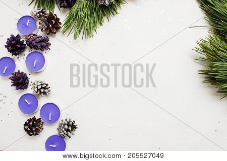 Festive background of New Year decoration. Small lavender tea candles with pine branch and strobila, top view and copy space. Holiday preparation, home and restaurant decor concept