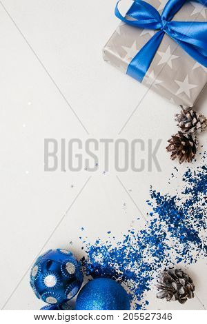 Festive background of Christmas decor and gifts. Wrapped in silver paper present, ornament blue balls on white table with spangles spread around, top view and copy space. Handmade decoration concept