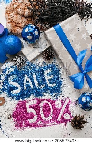 Sales on Christmas and New Year holidays, top view. Wrapped presents and different handmade ornaments with informative inscription of 50 pct discount. Festive and colorful background concept
