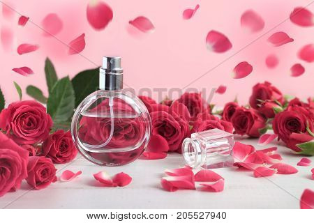 Rose perfume bottle surrounded by pink fresh rosebuds and falling petals. Floral feminine scent, beautiful dreamlike background.