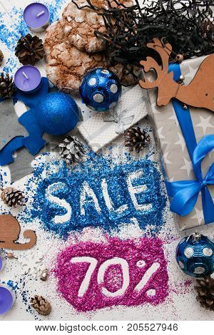 Sales on Christmas and New Year holidays, top view reversed. Festive decoration with informative inscription of 70 pct discount for shop-windows, shopping malls and advertizing background concept