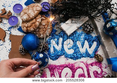 Firework sparkler on festive backdrop top view. Wrapped presents and different handmade ornaments with bright New Year inscription. Holiday decor and start of celebration concept