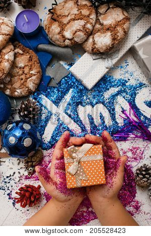 Christmas festive background of gifts top view. Little kid holds small present in purple glittering hands on bright xmas inscription and handmade decoration backdrop. Holiday and celebration concept