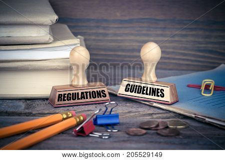 Regulations and Guidelines concept. Rubber Stamp on desk in the Office. Business and work background.