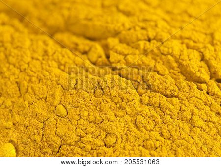 full close up image of turmeric used for cooking and health benefits such as anti inflammatory showing powered and root whit a with background for copy space