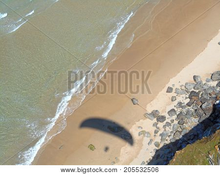 Shadow of a paraglider on Perranporth Beach, Cornwall