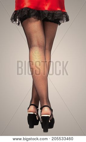 Young woman in short red dress high heel shoes and black sexy fishnet pantyhose stockings on her legs standing on the floor isolated.