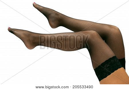 Raised up sexy female legs in fishnet pantyhose stockings isolated.