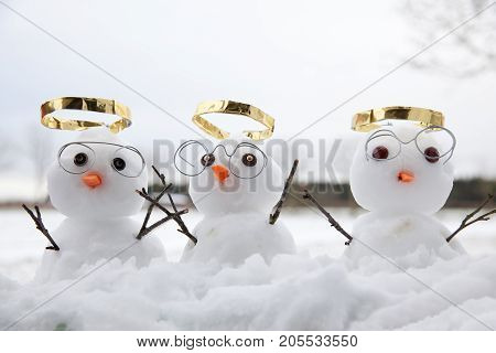 Three cute snowman angles with golden halos and reading glasses and their wooden twig arms in the air. Snow fall on the ground at winter poster