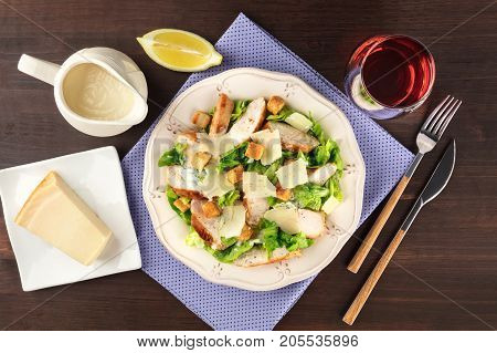 An overhead photo of a plate of chicken Caesar salad on a dark rustic background with a gravy boat, a slice of lemon, a fork and a knife, a piece of Parmesan cheese, a glass of wine, and copy space
