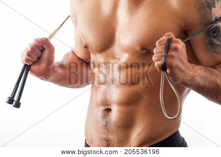 Cropped shot of muscular fitness model posing shirtless with jumping rope on shoulders. Studio shot of athletic man with naked torso.