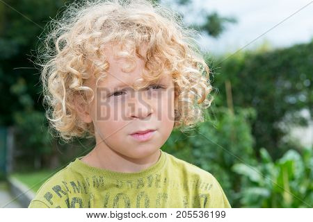 Portrait of a little boy with blond and curly hair