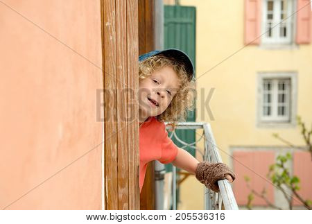 a little blond boy looking out the window
