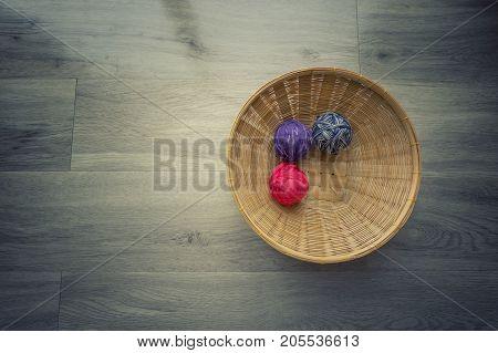 Multicolor clews in wicker basket on floor background.