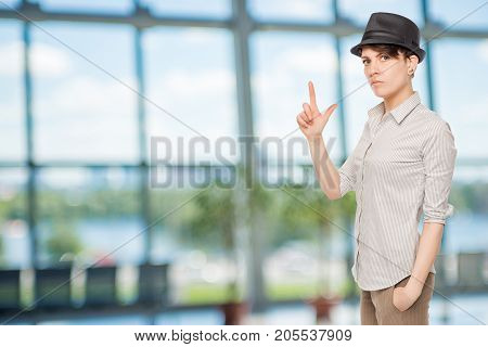 Serious Girl Holds Fingers Pistol And Wears A Black Hat In The Office