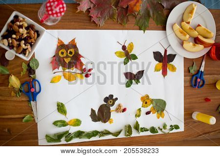Sweet child boy applying leaves using glue while doing arts and crafts in school autumn time