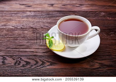 Cup with green tea and teapot on brown wooden background