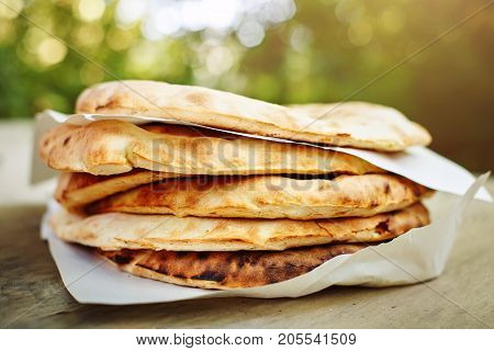 A stack of pita bread on a wooden table on the street.